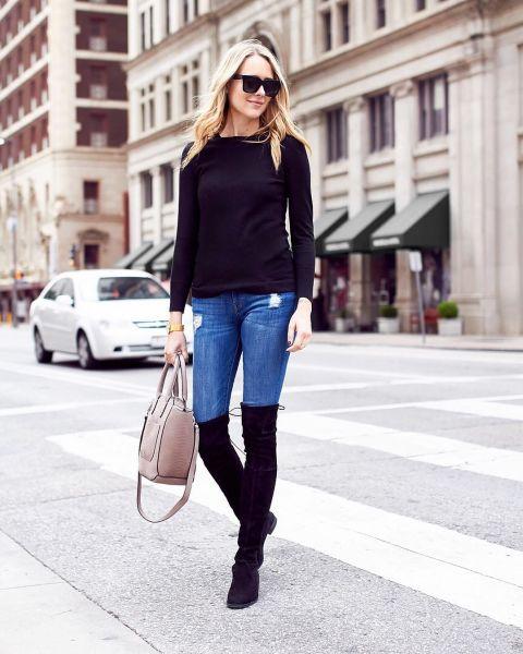 Эми Джексон в узких джинсах, черная футболка и ботфорты