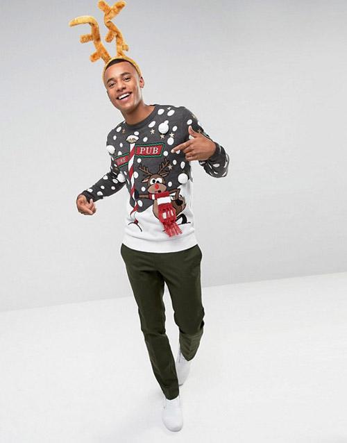 Парень в бело сером свитере с веселым новогодним оленем