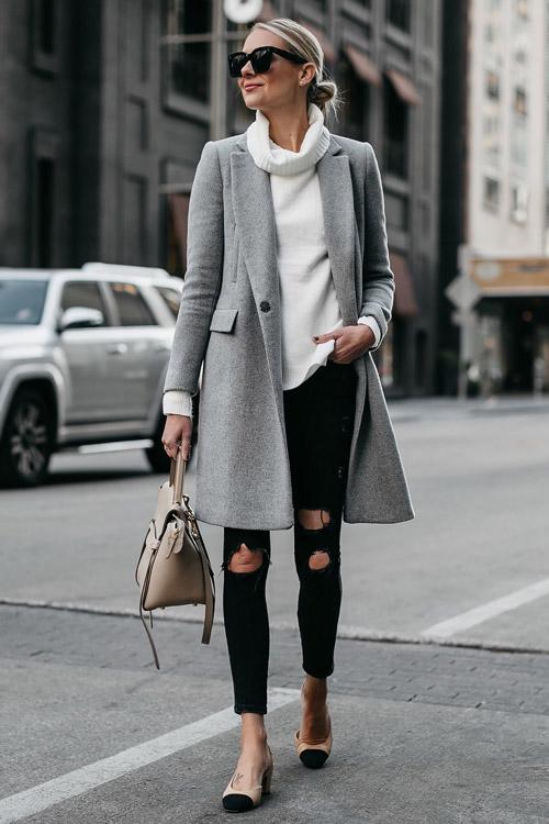 Девушка в черных джинсах, белом свитере и сером пальто