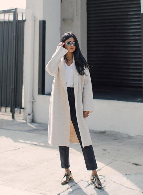 Девушка в укороченных брюках и светлом пальто