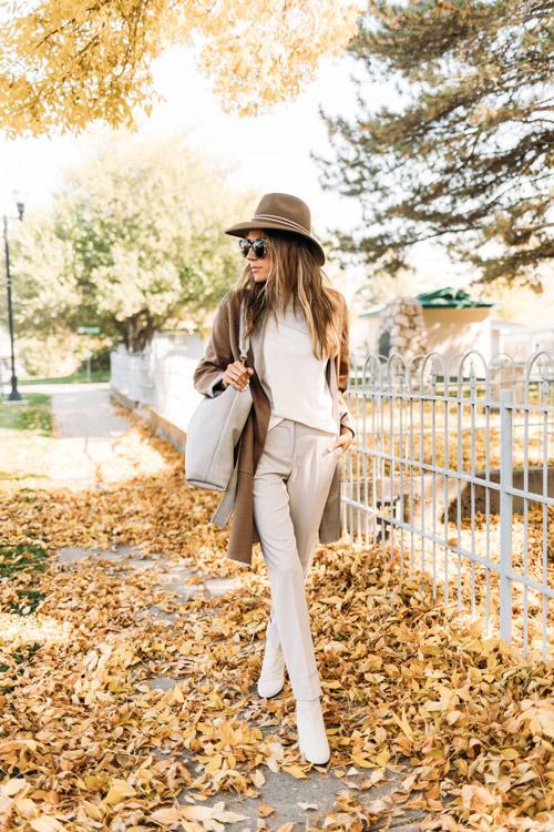 Девушка в светлых брюках, шляпе и пальто