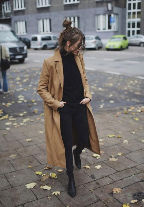 Девушка в черных джеггинсах, свитере и пальто цвета кемал