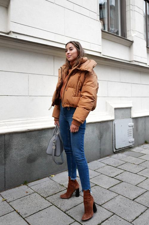 Девушка в синих джинсах, ботильонах и коротком пуховике