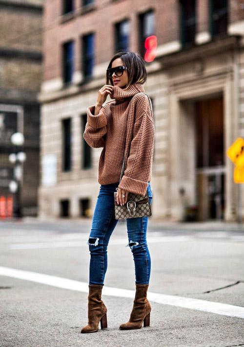Девушка в синих джинсах, ботильонах и вязаном свитере