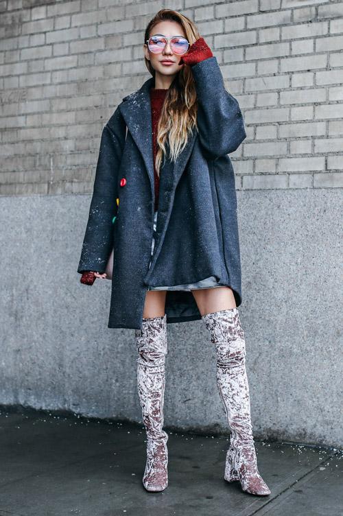 Девушка в высоких сапогах и синем пальто