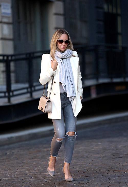 Девушка в рваных серых джинсах коротком белом пальто