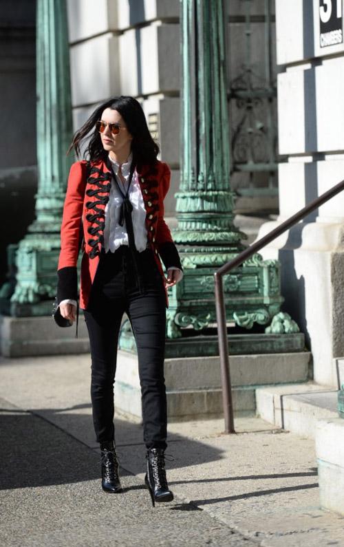 Девушка в черных брюках и жакете в стиле милитари
