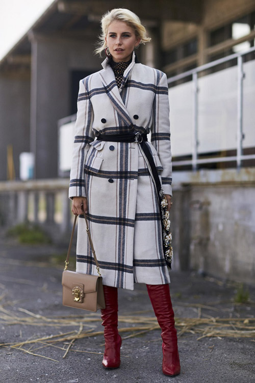 Девушка в белом пальто, красных сапогах и с черным дл иннным ремнем на поясе