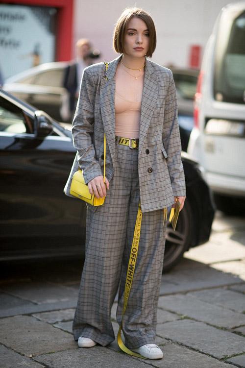 Девушка в брючном костюме в клетку и длинным желтым ремнем