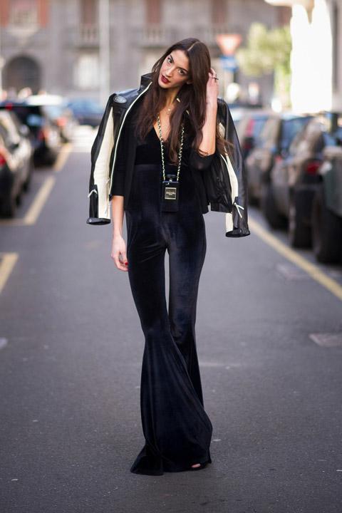 Девушка в черном бархатном комбинезоне клеш и кожаная куртка