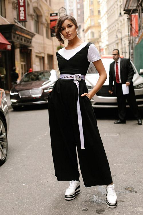 Девушка в черном комбинезоне и с белым длинным ремнем на поясе