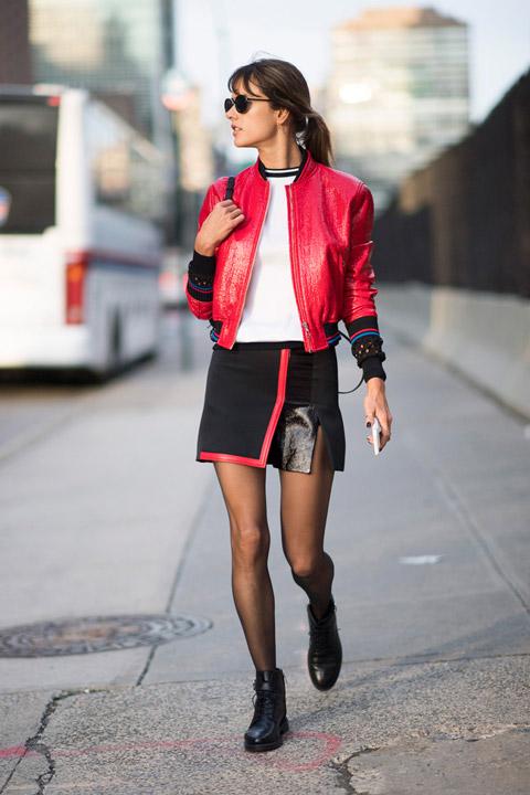 Девушка в черном комбинированой юбке мини, белая футболка и красный бомбер