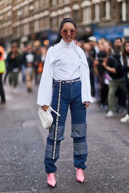 Девушка в джинсах, белой водолазке, розовых ботильонах и длинным ремнем на поясе