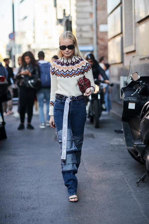 Девушка в джинсах, свитере и с длинным ремнем на поясе