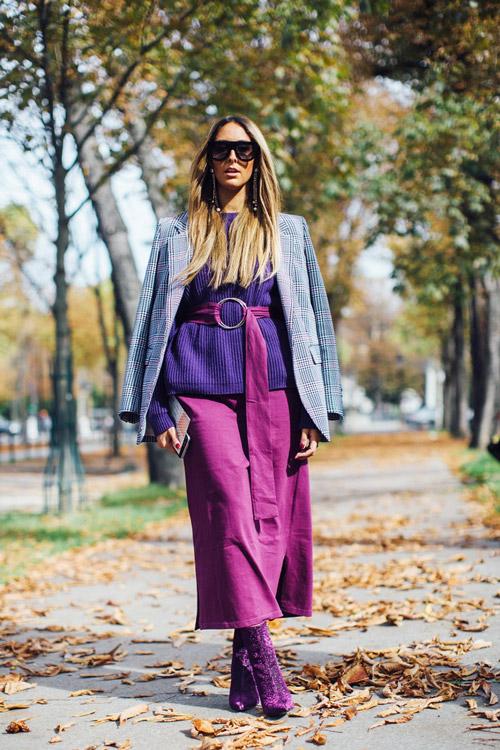 Девушка в фиолетовой юбке, пиджаке и с фиолетовым длинным ремнем