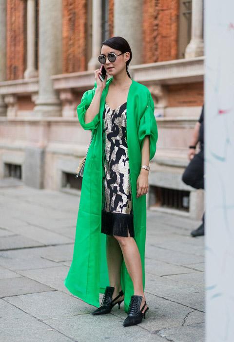 Девушка в коктейльном платье с бахромой, зеленый плащ и черные туфли