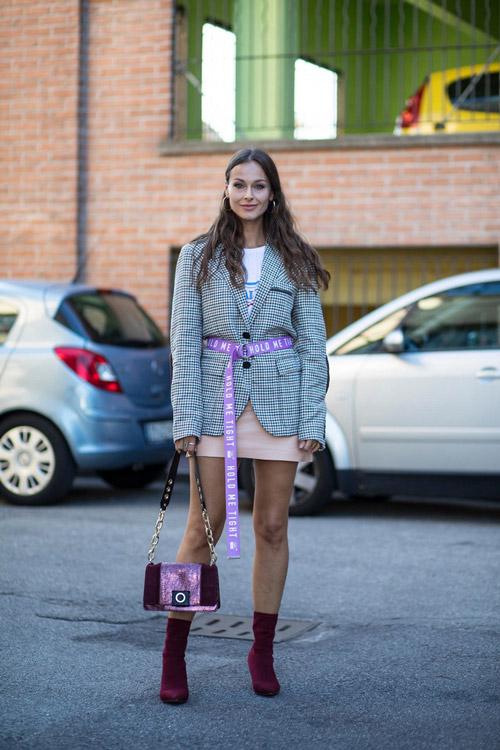 Девушка в мини юбке клетатом пиджае и с фиолетовым длинным ремнем на поясе