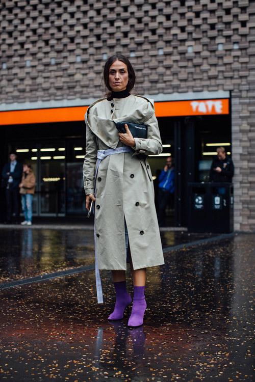 Девушка в плаще, фиолетовых ботильонах и длинным ремнем на поясе