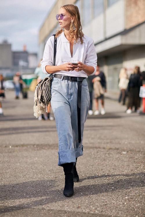 Девушка в подвернутых джинсах, черных ботильонах и длинным ремнем