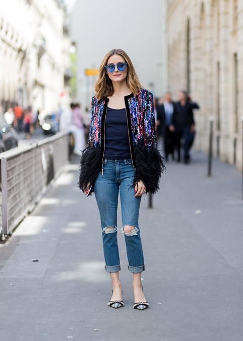 Девушка в рваных джинсах, черный топ и куртка с пайетками