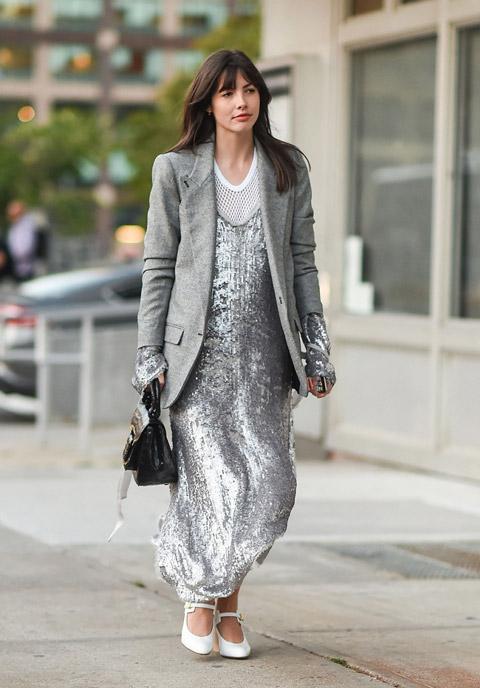 Девушка в серебристом платье с блестками и серы пиджак