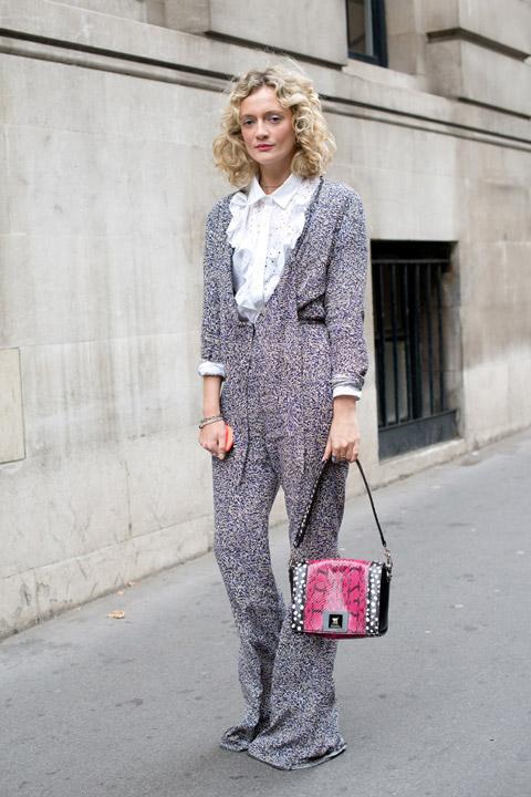 Девушка в сером комбинезоне, белая блузка с рюшами и сумочка