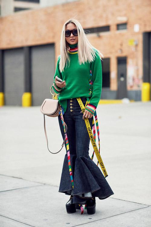 Девушка в зеленом свитере, джинсах клеш и длинным желтым ремнем на поясе