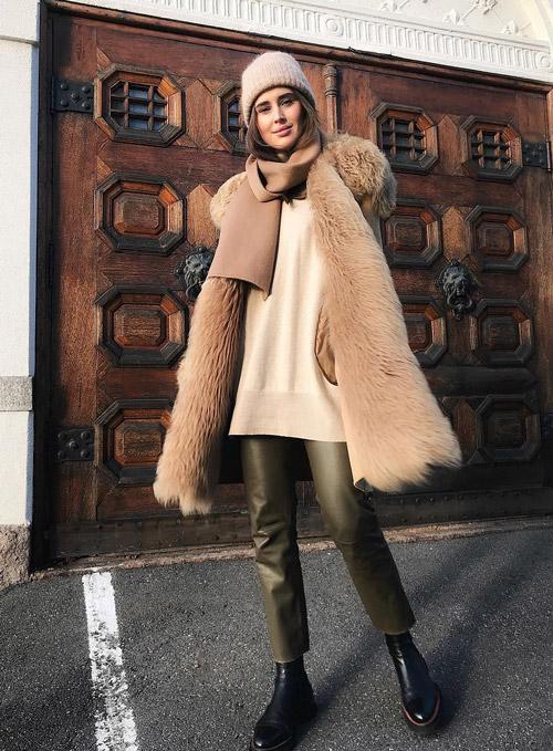 Девушка в кожаных брюках, светлая туника и бежевая шапка, шарф