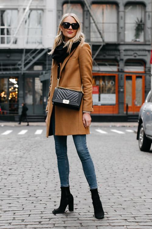 Девушка в облегающих джеггинсах, коричневое пальто и черные ботильоны и сумка