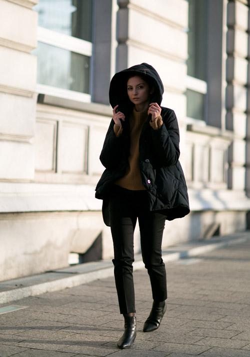 Девушка в черных капри и пуховик с капюшоном