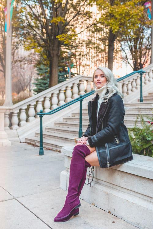 Девушка в черной дубленке и ботфорты цвета фуксии без каблука