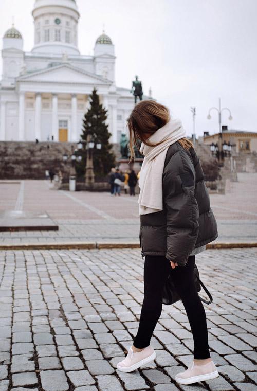Девушка в черных лосинах, коричневый пуховик, слипоны и шарф