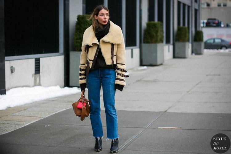 Девушка в широких джинсах, теплый свитер и бежевый полушубок