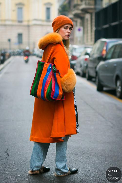 Девушка в оранжевом пальто с меховой отделкой, шапка и голубые джинсы