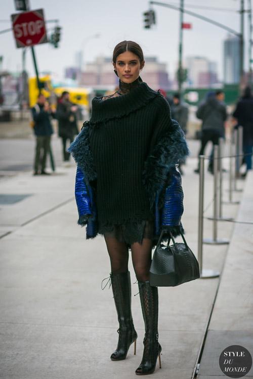 Девушка в вязаной тунике и синяя куртка, сапоги н шнуровке и шпильке