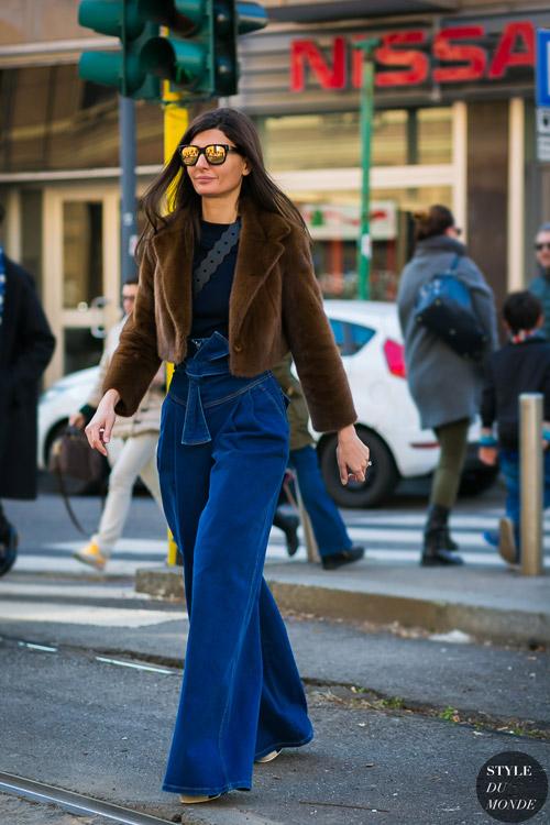 Девушка в широких джинсах клеш и маленький коричневый полушубок