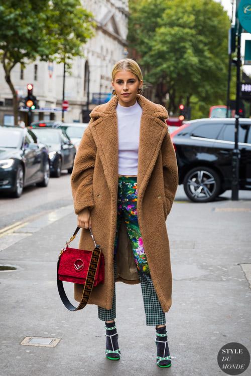 Девушка в капри с принтом, белая водолазка и коричневая шуба, красная сумк и босоножки