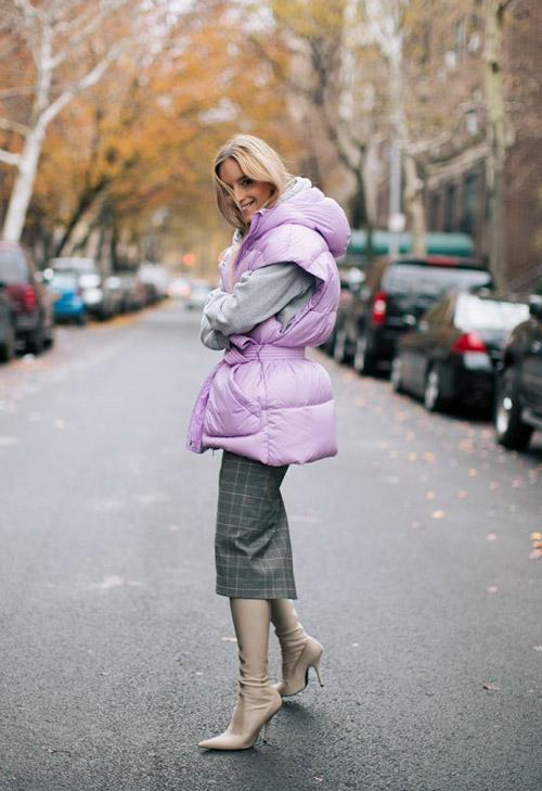 Девушка в серой юбке карандаш, светлая синтепоновая жилетк и бежевые сапоги с острым носом