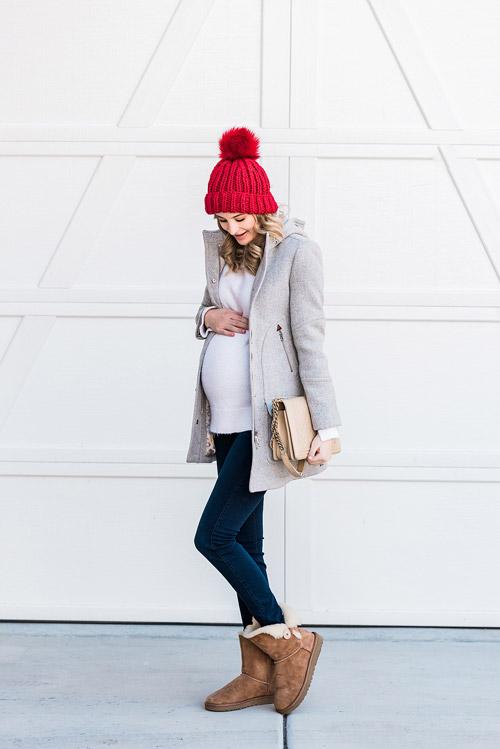 Девушка в джеггинсах, белая кофта, сероу пальто, угги и красная шапка