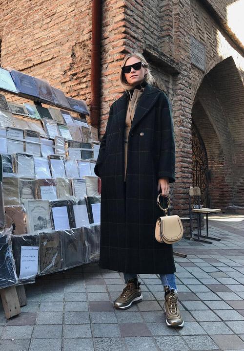 Девушка в длинном пальто в клетку, коричневые кроссовки и джинсы