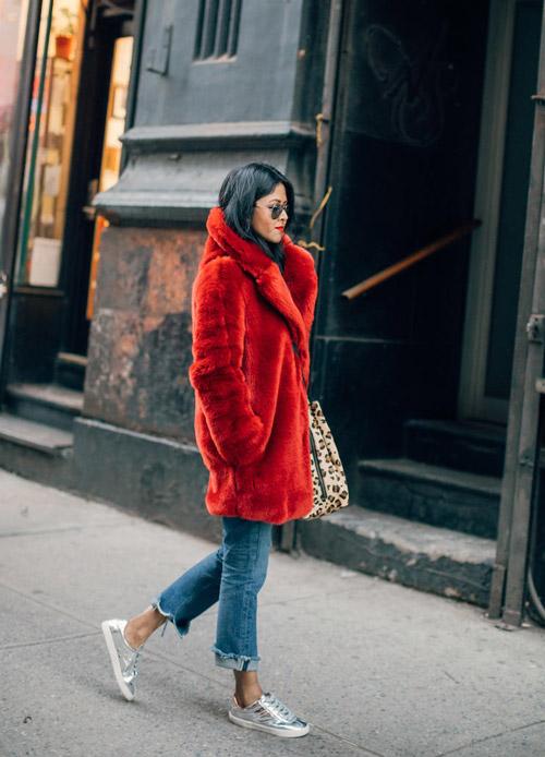 Девушка в укороченных джинсах, серебристые кеды и красная шуба