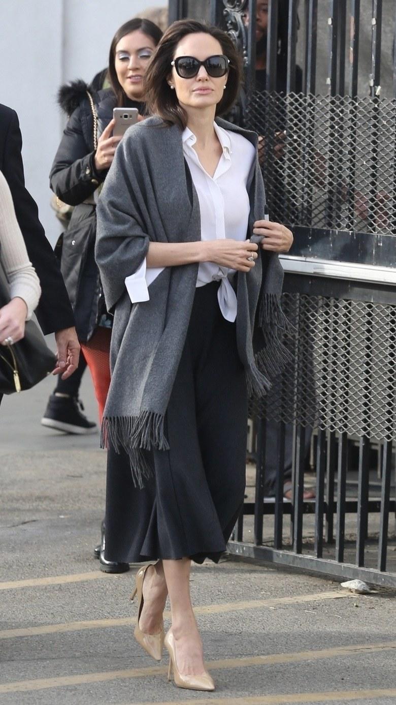 Анджелина Джоли в сером палантине, белой рубашке с узлом и черной юбке миди