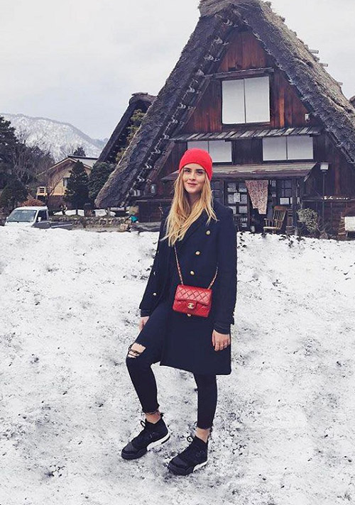 Девушка в черных джинсах, кроссовках, пальто и красной шапке