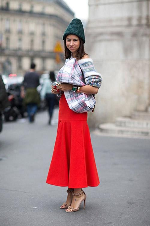 Девушка в красной юбке, бежевых босоножках и забавной шапке