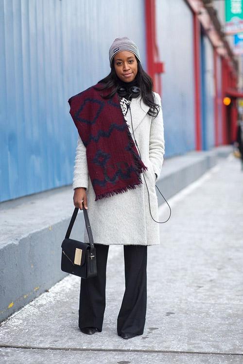 Девушка в пальто, длинных черных брюках и полосатой шапке