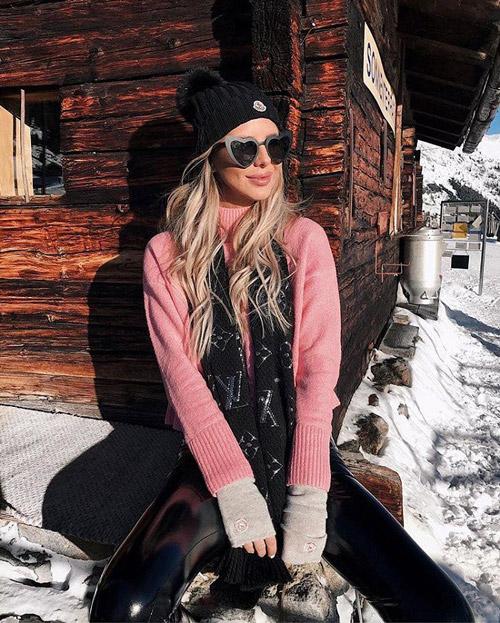 Девушка в розовом свитере, черных брюках и шапке