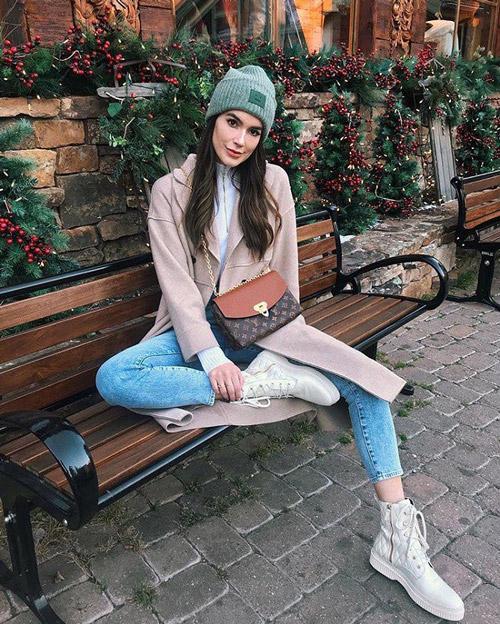 Девушка в синих джинсах, пальто, белых ботинках и шапке