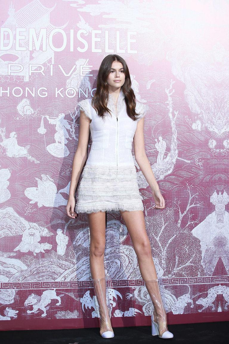 Кайя Гербер в белом коктейльном платье и прозрачных ботильонах