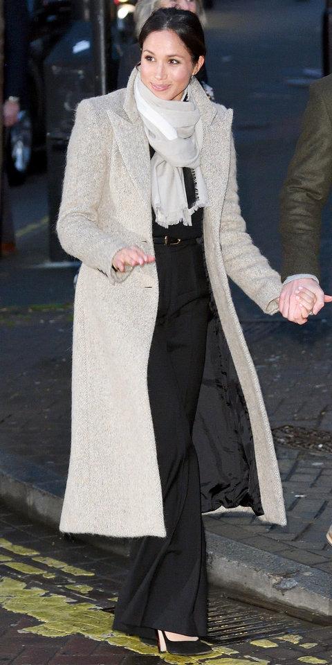 Меган Маркл в сером длинном пальто, расклешенных черных брюках и шарфе