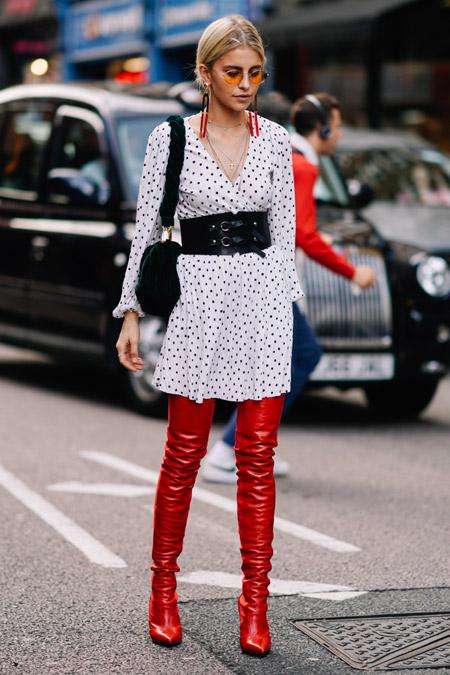 Девушка в белом платье в мелкий горошек с поясом и красные ботфорты
